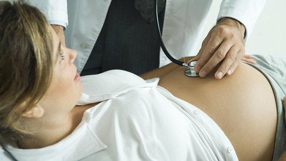 Ein Arzt hört einer schwangeren Frau den Bauch mit einem Stethoskop ab.