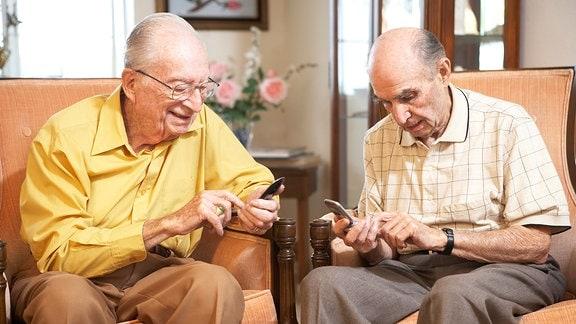 Zwei Senioren sitzen in Sesseln und sehen auf ihre Telefone