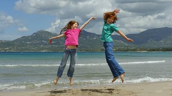 Zwei Kinder springen am Strand in die Luft.