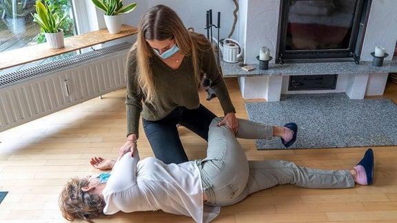 Erste Hilfe Massnahmen unter Corona-Bedingungen, Stabile Seitenlage, nach einem Unfall im der Wohnung, mit Mund-Nase-Maske