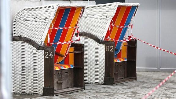 Die Strandkörbe eines Restaurants sind aufgrund der Corona-Krise mit Absperrband geschlossen
