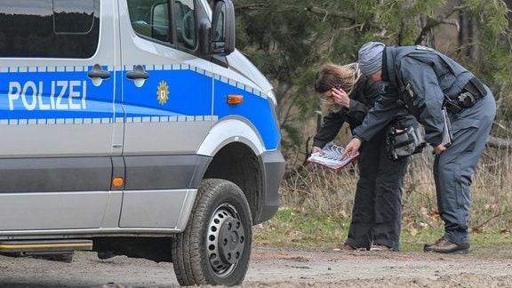 Beamte der Kriminalpolizei stehen während der Suche nach der vermissten Rebecca an einem Waldgebiet im Landkreis Oder-Spree.