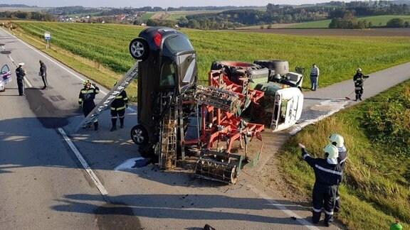 Auto steht senkrecht und ist in Traktoranhänger verkeilt, Feuerwehrleute sind im Einsatz