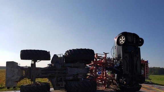 Schattenriss eines Autos, das senkrecht steht und in Traktoranhänger verkeilt ist.