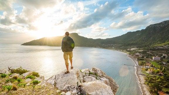 Ein Mann steht an der Küste auf einem Felsen.