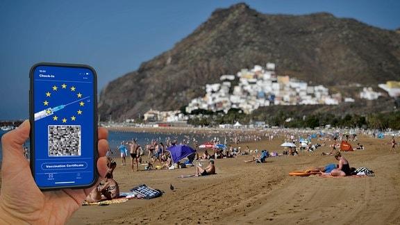 Symbofoto Impfprivilegien, Smartphone mit digitalem europäischen Impfpass mit QR-Code, Strandleben