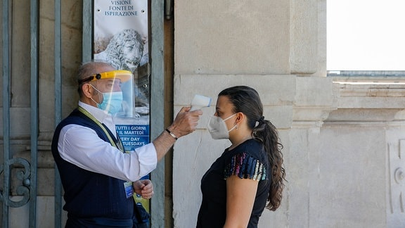 Bei einer Frau wird Fieber gemessen