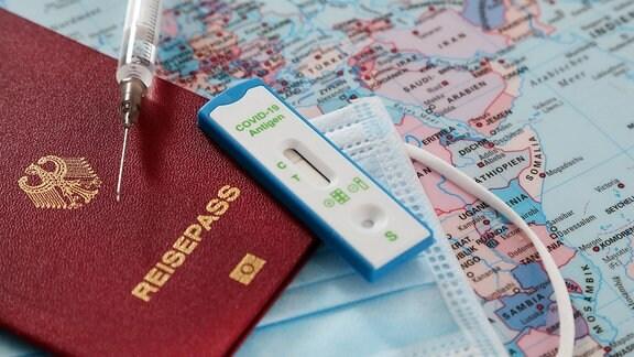 Reisepass, Schutzmaske, Schnelltest und Spritze auf einer Landkarte