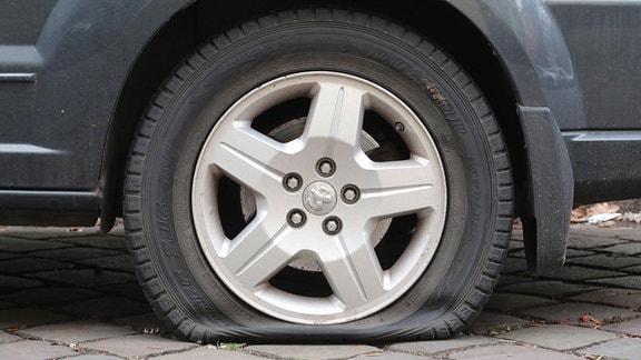 An einem Auto sind der Lack zerkratzt und die Reifen zerstochen.