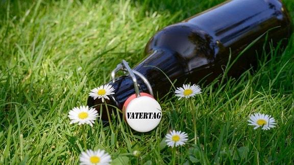 Vatertag steht auf dem Schnappverschluss einer leeren Bierflasche, die auf einer Wiese liegt.