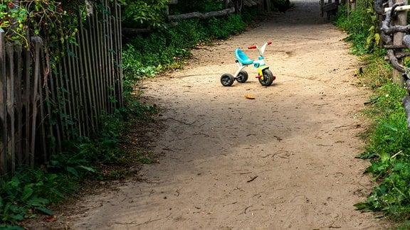 Verlassenes Dreirad auf einem Feldweg.
