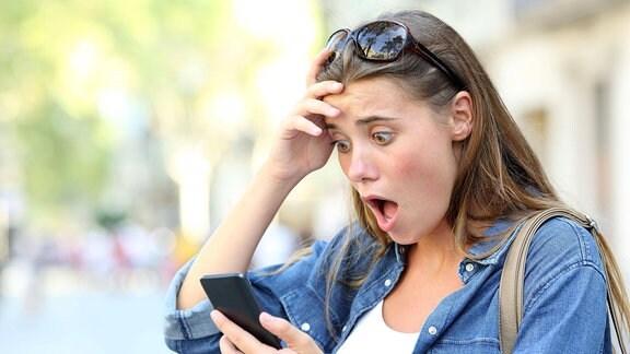 Schockierte junge Frauv schaut aufs Smartphone.