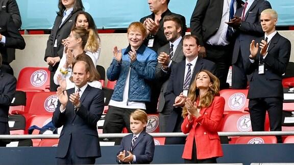 Prinz William, Herzog von Cambridge mit Ehefrau Catherine, Herzogin von Cambridge und Sohn George, dahinter David Beckham und Ed Sheeran auf der Tribuene.