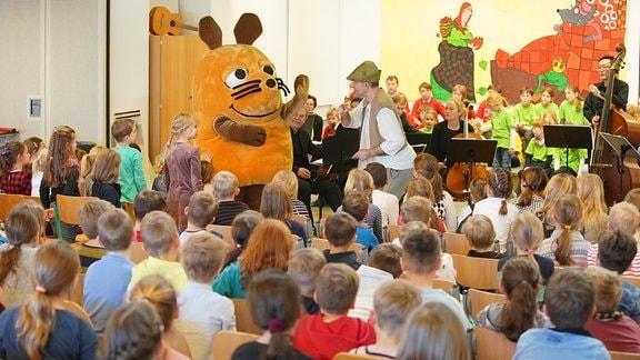 """Die Maus aus der """"Sendung mit der Maus"""" steht mit MDR-Musikvermittler Ekkehard Vogler im Kostüm auf der Bühne eines MDR-Clara-Schulkonzerts in Radeburg."""