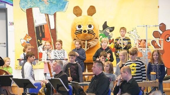 """Die Maus aus der """"Sendung mit der Maus"""" steht mit Schulkindern auf der Bühne eines MDR-Clara-Schulkonzerts in Radeburg und macht Musik."""