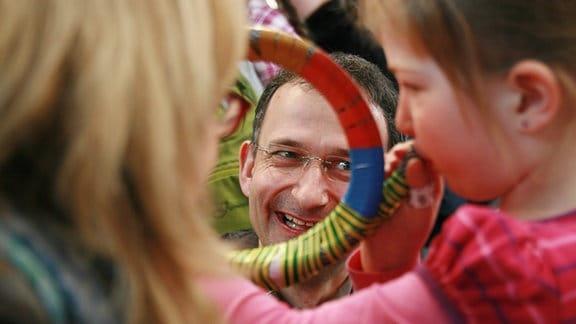 MDR-Musikvermittler Ekkehard Vogler lacht hinter Kind mit selbstgebautem Horn