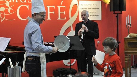 """MDR-Musikvermittler Ekkehard Vogler trägt Schürze und Kochmütze und schlägt mit einem Schneebesen in ein Nudelsieb, neben ihm ein Juge, der ein """"Bratpfannen-Xylophon"""" schlägt, im Hintergrund ein MDR-Klarinettist."""