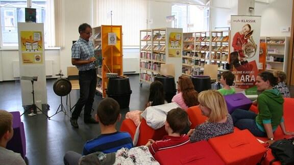 """Ekkehard Vogler zeigt seinem Publikum das Buch bei der musikalischen Lesung von """"Das Nian-Monster""""."""