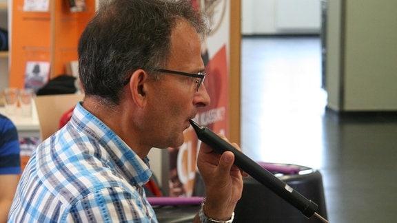"""Ekkehard Vogler bläst in eine schwarze Flöte bei der musikalischen Lesung von """"Das Nian-Monster""""."""