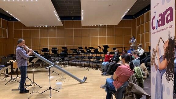 Musikvermittler Ekkehard Vogler spielt auf einem selbstgebauten Alphorn
