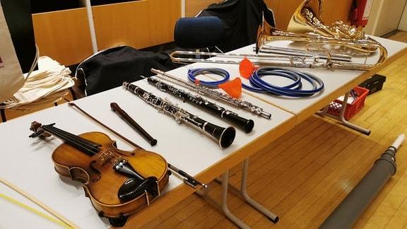 Verschiedene Musikinstrumente liegen nebeneinander auf einem Tisch