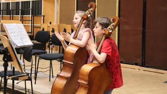 """Kinder der Streicherklasse der Freien Grundschule """"Clara Schumann"""" in Leipzig klatschen bei MDR KLASSIK in die Hände, neben ihnen Notenständer und Celli."""