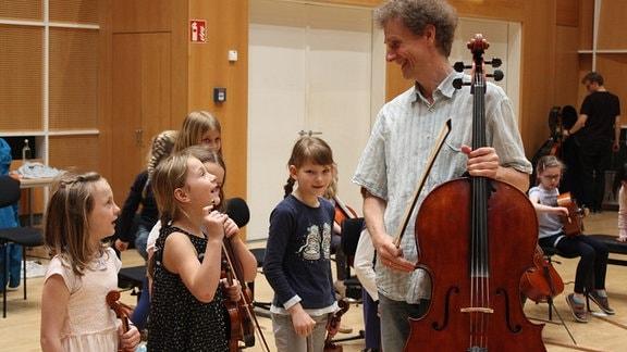 """Kinder der Streicherklasse der Freien Grundschule """"Clara Schumann"""" mit ihren Instrumenten und einem Musiker von MDR KLASSIK."""