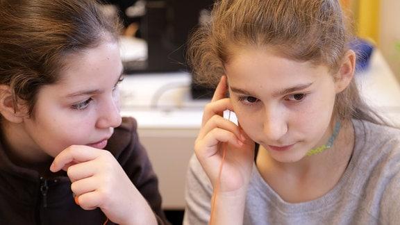 Zwei Mädchen hören etwas über Kopfhörer.