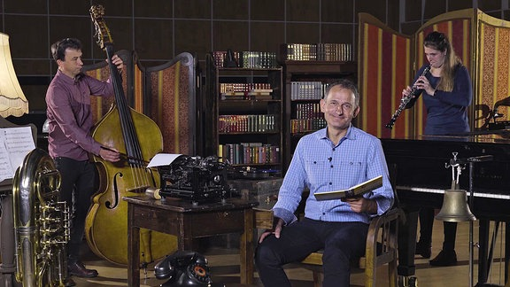 Ein Mann sitzt mit einem Buch im Sessel, im Hintergrund ein Mann mit Kontrabass und eine Frau mit Oboe.