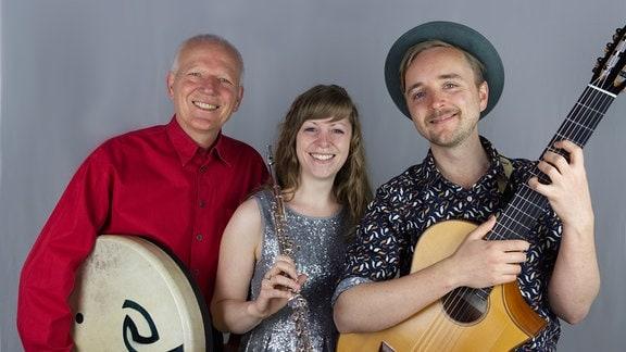 Eine Frau mit Querflöte, ein Mann mit Gitarre und ein Mann mit Trommel.