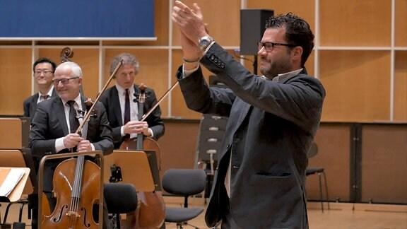 Ein Mann (Komponist Aristides Strongylis) klatscht in die Hände, im Hintergrund lachende Orchestermusiker.