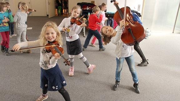 Drei Mädchen albern mit ihren Streichinstrumenten.