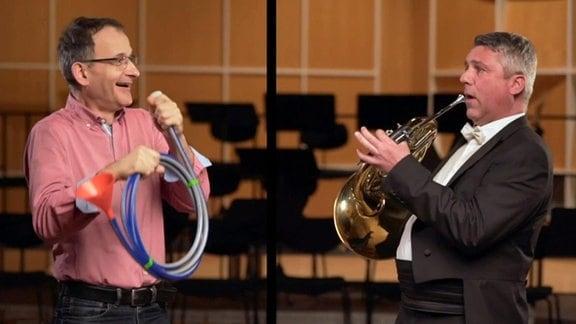 """Zwei Männer sehen sich erstaunt freudig an. Einer hält ein """"echtes"""" Horn, einer ein Horn aus einem Gartenschlauch in der Hand."""