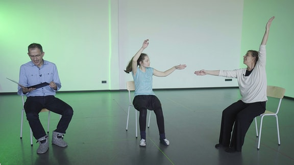 """MDR-Musikvermittler Ekkehard Vogler liest, Tanzpädagogin Brit Böttger und die Schülerin Flora machen Bewegungen zur Musik von """"Karneval der Tiere""""."""