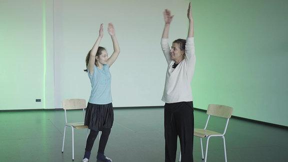 """Tanzpädagogin Brit Böttger und die Schülerin Flora machen Bewegungen zur Musik von """"Karneval der Tiere""""."""