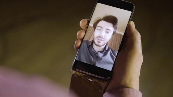Das Bild des Dirigenten Martijn Dendievel ist auf einem Smartphone zu sehen.