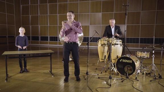 """MDR-Musikvermittler Ekkehard Vogler, MDR-Schlagzeuger Thomas Winkler und der Schüler Julius spielen Rhythmen zur Geschichte von """"Karneval der Tiere""""."""