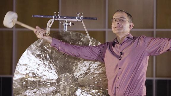 MDR-Musikvermittler Ekkehard Vogler mit einem Schlägel vor einem großen Tamtam.