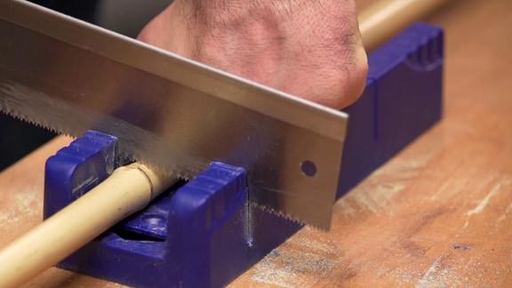 Ein Bambusrohr wird mit einer Handsäge zersägt.
