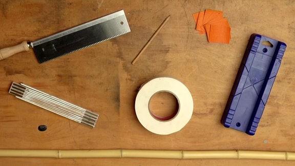 Auf einem Tisch liegt Werkzeug für den Bau einer Panflöte aus Bambus.