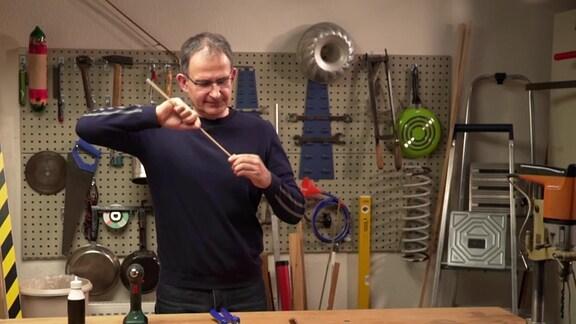 MDR-Musikvermittler Ekkehard Vogler befestigt einen Stab in einem Korken.