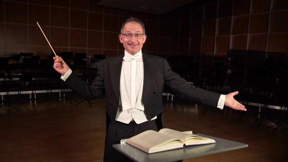 MDR-Musikvermittler Ekkehard Vogler im Frack mit einem selbstgebastelten Taktstock.
