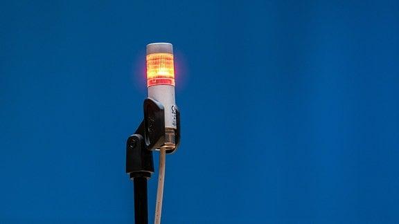Vor blauem Hintergrund leuchtet eine rote Lampe als Zeichen, dass eine Aufnahme läuft.