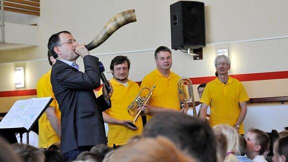 MDR-Musikvermittler Ekkehard Vogler spielt vor Bläsern des MDR SINFONIEORCHESTERS ein Horn.