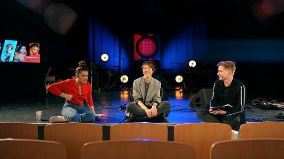 Chris Löwe sitzt mit den Sängerinnen Antje Schomaker und Emily Roberts auf dem Rand einer Bühne