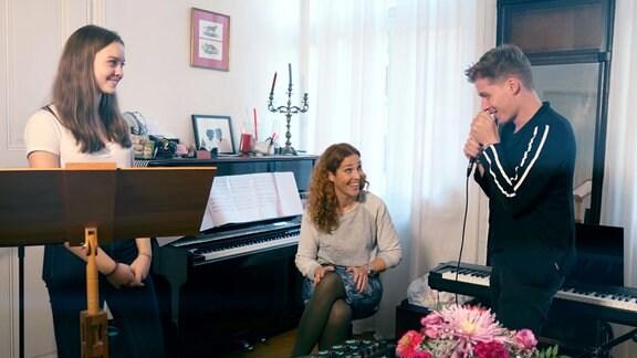 Ein Mädchen steht an einem Notenständer, eine Frau sitzt am Klavier, MDR-Moderator Chris Löwe spricht in ein Mikrofon