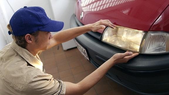 Ein Mechaniker wechselt an einem Kfz den Scheinwerfer.
