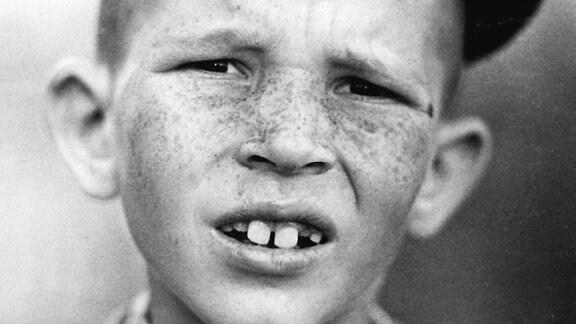 Sommersprossiger Junge mit schwarzer Schiebermützer und auffälligen Schneidezähnen