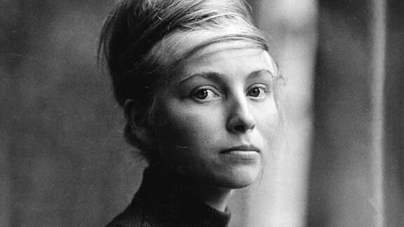 Portät einer jungen Frau mit langem, blondem Haar, das zu einer turmartigen Frisur um den Kopf geschlungen ist