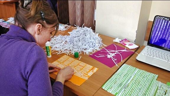 Eine Frau an einem Tisch. Sie klebt aus einem Haufen geschredderten Papiers einzelne Streifen auf ein Blatt.